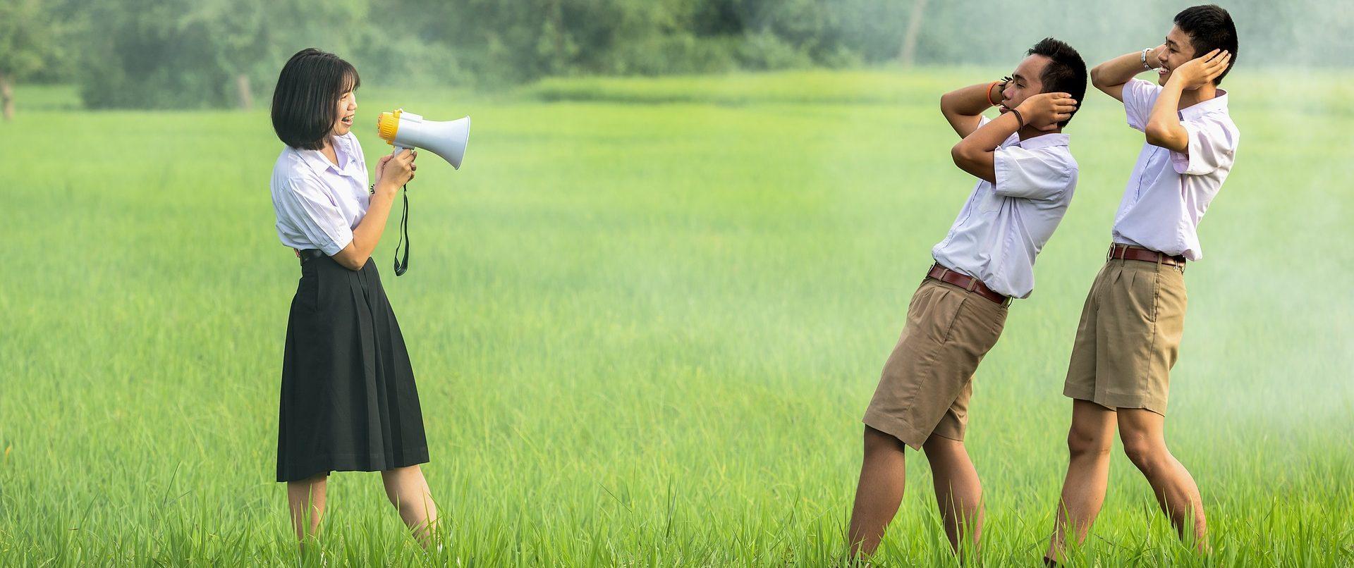 Hangosbeszélőn kiabáló lány, akitől két férfi ilyed meg