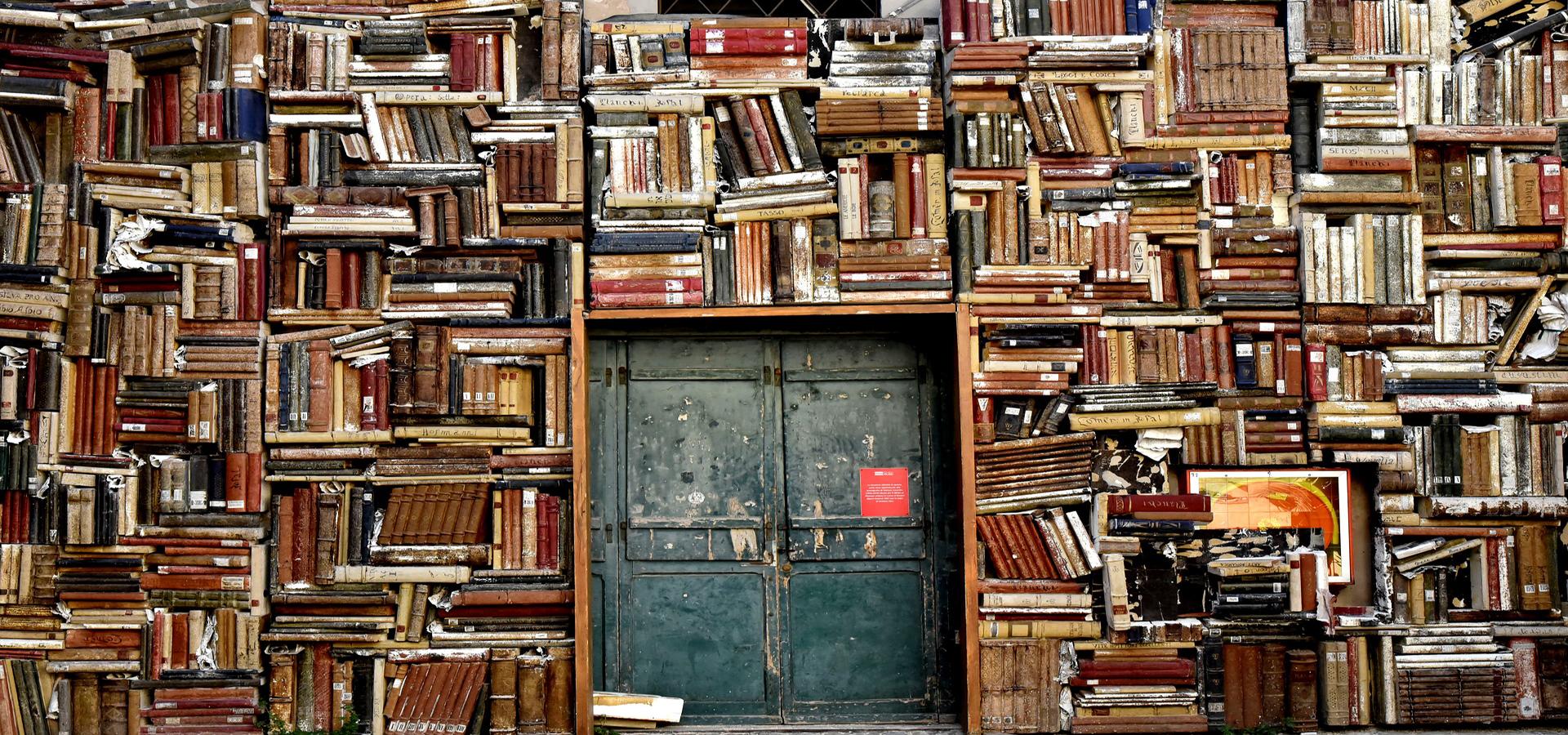 Könyvekkel telezsúfolt könytári fal, melyen van egy kopott ajtó