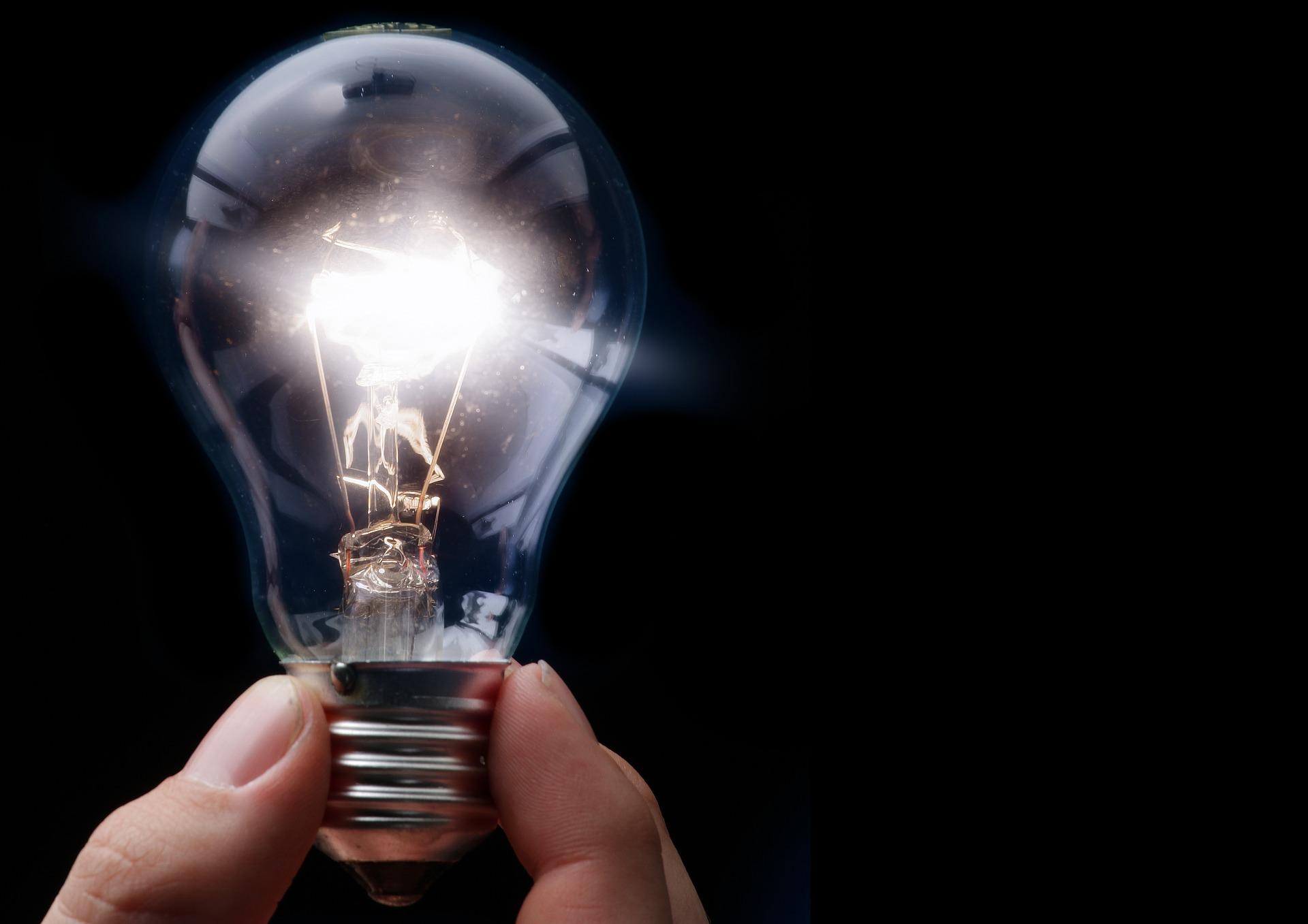 Felkapcsolt villanykörte egy emberi kézben